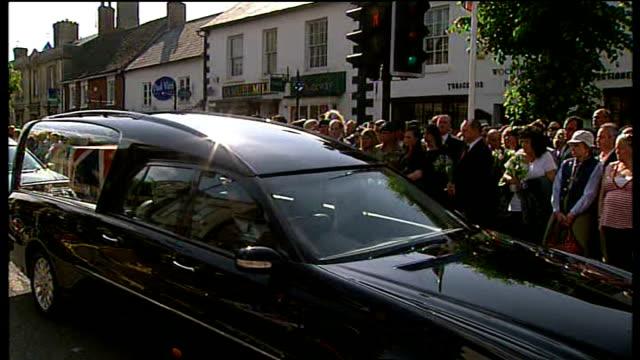 royal marines killed in afghanistan repatriated; england: wiltshire: wootton bassett: ext various of people holding flowers cortege of hearses... - 英国海兵隊点の映像素材/bロール