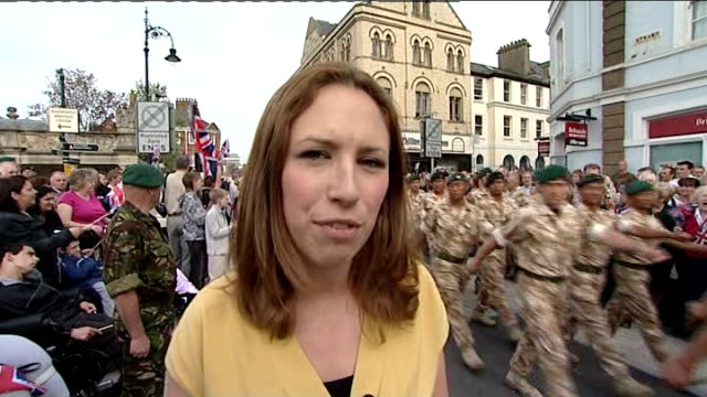royal marines parade through streets of barnstable; england: devon: ext reporter to camera as troops march behind school children waving union jack... - ホームカミング点の映像素材/bロール