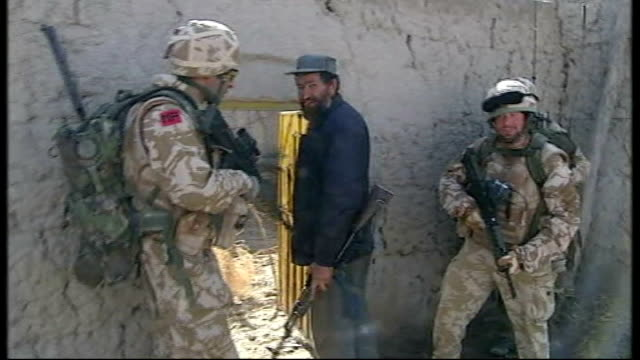 royal marines training afghan police in sangin; british troop and afghan police officer knocking on door of house that they want to search afghan... - 英国海兵隊点の映像素材/bロール