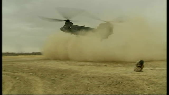 royal marines training afghan police in sangin; ext chinook helicopter landing at base back view afghan police officers along british soldiers... - 英国海兵隊点の映像素材/bロール