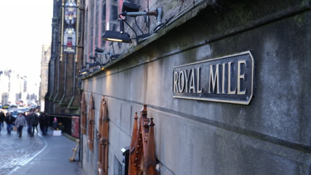 4k dolly: royal mile street sign in edinburgh, scotland with tourists walking - royal mile stock videos and b-roll footage