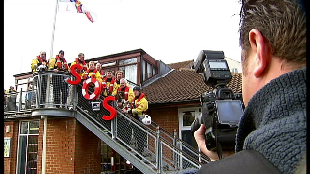 royal national lifeboat institution struggle to cope with increased demand ext rnli crew posing with sos sign on steps of station and taking part in... - sos stock videos and b-roll footage