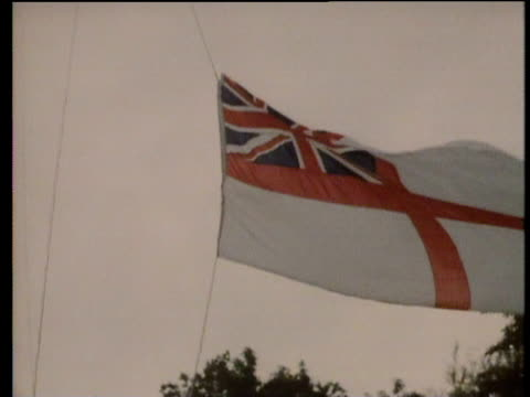 royal navy flag being lowered from flag pole chatham - bandiera del regno unito video stock e b–roll