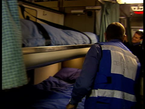 HMS Illustrious General views of sleeping quarters including bunks and crew members with personal belongings such as paperback books mp3 players and...