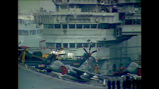 vídeos de stock e filmes b-roll de royal navy personnel to lose their jobs 1982 royal navy aircraft carrier leaving port sailors waving from deck of ship fighter aircraft taking off... - ilhas malvinas