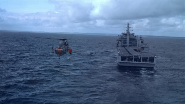 AIR TO AIR, Royal navy rescue helicopter landing on aircraft carrier, ground crew carrying stretcher, France