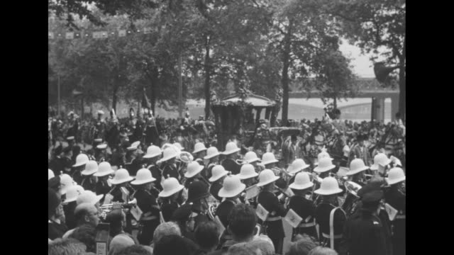 royal navy sailor stands guard in front of crowd on street / procession of horse-drawn carriages leaves buckingham palace passing the queen victoria... - 連隊点の映像素材/bロール