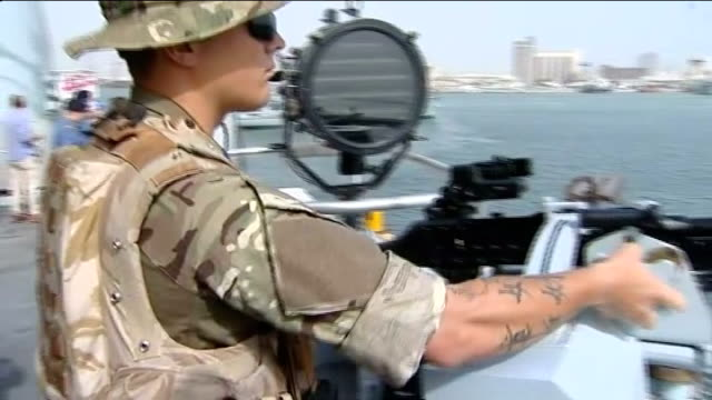 royal navy takes part in major exercise in the gulf; bahrain: persian gulf: ext soldier on board ship adjusting machine gun ship entering port... - british military stock-videos und b-roll-filmmaterial