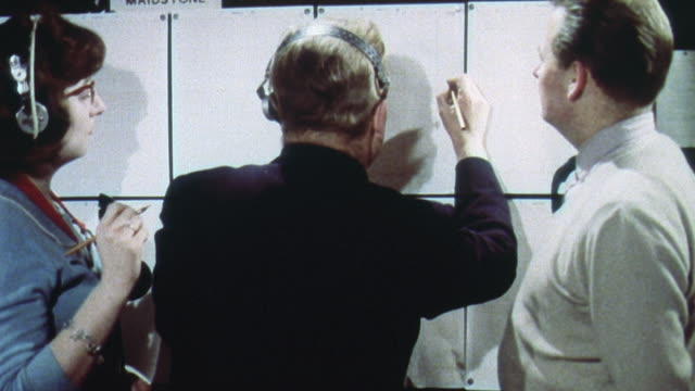 1962 MONTAGE Royal Observer Corps technicians analyzing and plotting nuclear fallout decay and drift information on maps and grids in Cold War training exercise / United Kingdom