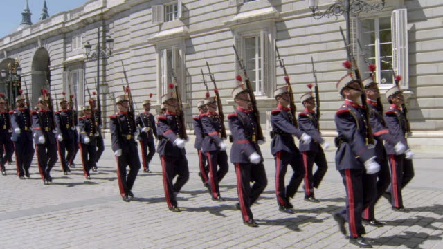 vídeos y material grabado en eventos de stock de royal palace guards marching to music at palacio real de madrid, the royal palace in madrid, spain - uniforme