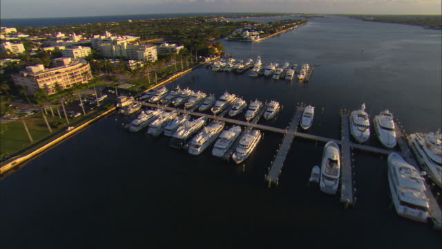 low aerial royal park bridge, yachts in marina and waterfront houses at palm beach, florida, usa - jachthafen stock-videos und b-roll-filmmaterial