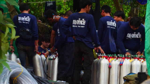 Royal Thai Navy work on refilling scuba tanks for the rescue mission at the base of rescue operations outside the cave network where boys among a...