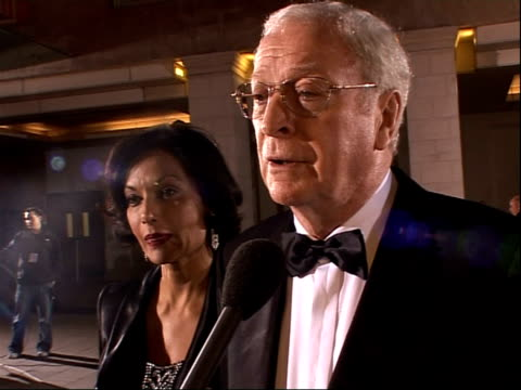 red carpet arrivals sir michael caine interview with wife shakira standing alongside sot on rereleasing batman so it qualifies for the oscars / on... - shakira caine stock videos and b-roll footage
