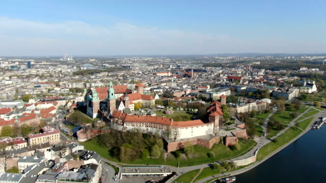 royal wawel gothic cathedral in krakow, poland, with wawel castle, yard, park, tourists and vistula river. aerial 4k reveal video at sunset in spring. old city with st. mary church in the background - poland stock videos & royalty-free footage