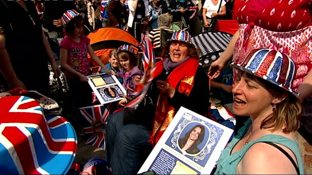 crowds camp outside westminster abbey; england: london: westminster abbey: ext royal fans, some wearing union jack hats, singing 'we're getting... - pavement点の映像素材/bロール