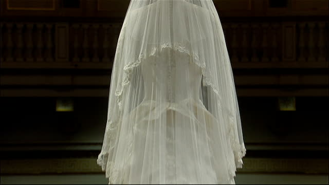 vídeos de stock, filmes e b-roll de royal wedding dress on display at buckingham palace back views of wedding dress veil and train / close shots of dress / close shots of diamond... - véu