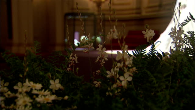 stockvideo's en b-roll-footage met royal wedding dress on display at buckingham palace royal coat of arms on wall pull out wedding dress displayed on headless mannequin / more general... - onthoofd