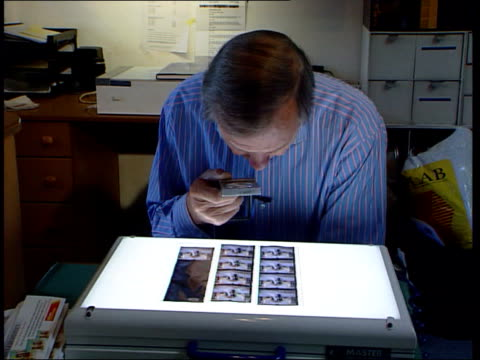 edward & sophie: aftermath; a)nn: paul davies itn england: london: int geoffrey shakerley inspecting negatives with magnifying glass - negatives stock videos & royalty-free footage