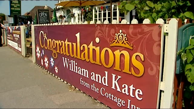 Street parties Berkshire Bucklebury Man drilling bunting to pub exterior Pub sign reading 'Congratulations William and Kate' Man putting up bunting