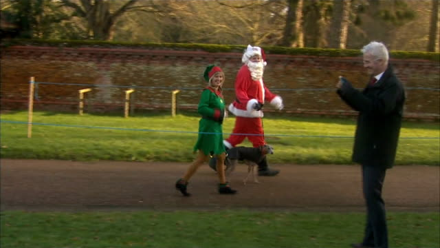 royals at church at sandringham; england: norfolk: sandringham ext father christmas and elf along with dog / general views of people waiting / royal... - イーストアングリア点の映像素材/bロール