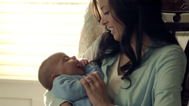 stockvideo's en b-roll-footage met royalty free stock footage of baby being held by mother in a rocking chair. - schommelen schommelstoel