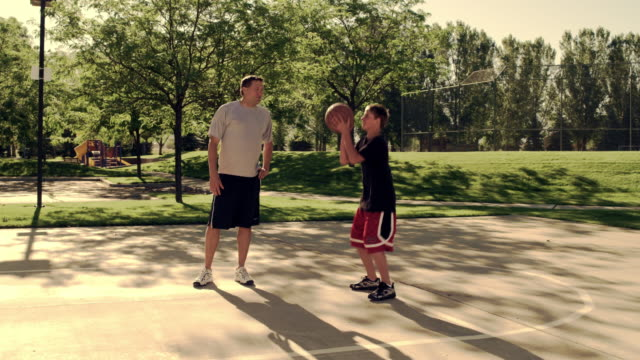 Royalty Free Stock Footage of Dad and boy playing basketball.
