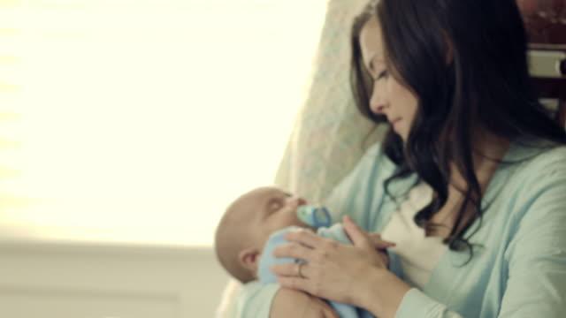stockvideo's en b-roll-footage met royalty free stock footage of mother and baby in a rocking chair. - schommelen schommelstoel