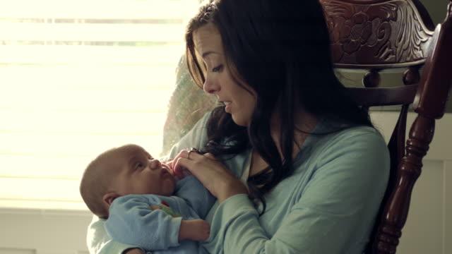 stockvideo's en b-roll-footage met royalty free stock footage of mother holding her baby in a rocking chair. - schommelen schommelstoel