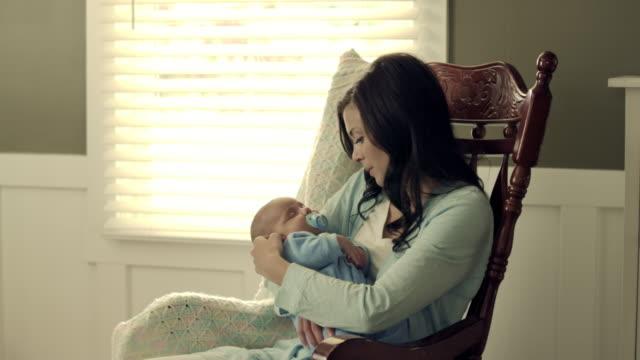 stockvideo's en b-roll-footage met royalty free stock footage of mother rocking her baby to sleep in a rocking chair. - schommelen schommelstoel