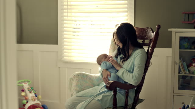 vidéos et rushes de royalty free stock footage of mother with baby in a rocking chair. - bercement