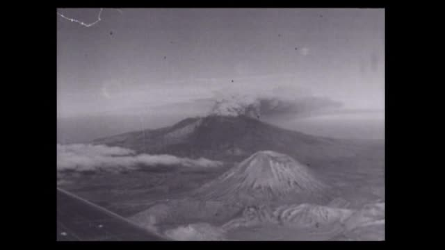 vidéos et rushes de ruapehu volcano erupting for the first time in 400 years in september 1945 with aerial view and wide shots of explosive clouds emitting from crater... - répandre