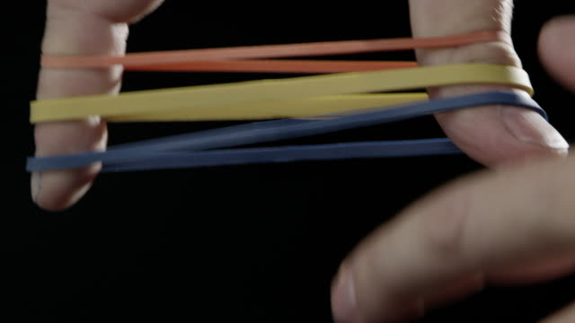 Rubber bands slow motion black background caucasian human hand colorful