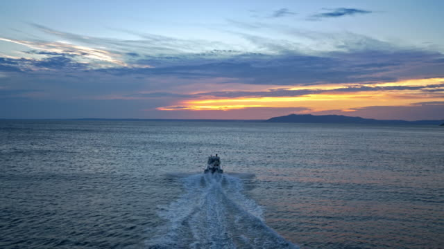 AERIAL Rubber boat riding on sea at sunset