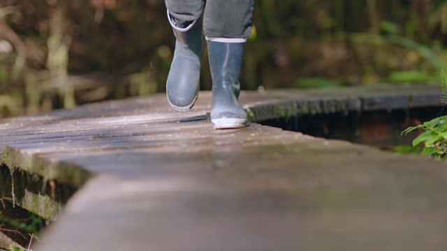 SLO MO. Rubber boots walk towards camera on elevated wooden path.