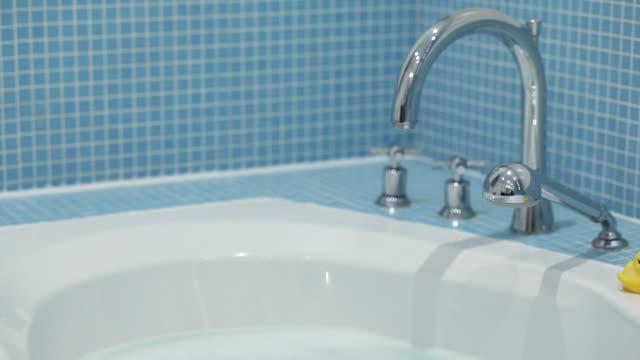 Rubber ducks on side of bath