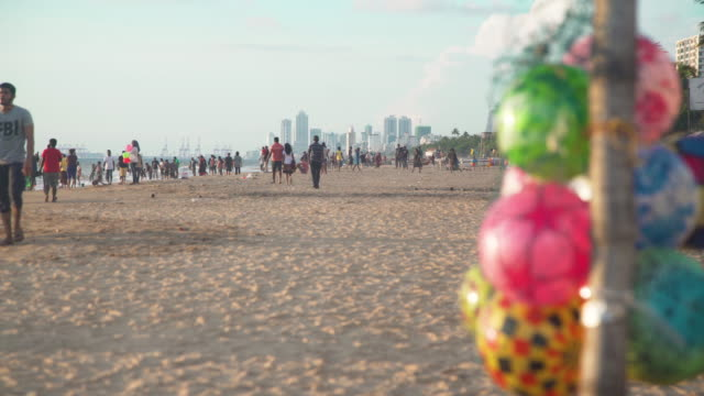 stockvideo's en b-roll-footage met rubber ring float stall at sri lanka beach with colombo skyline on the background. mount lavinia - rubber ring
