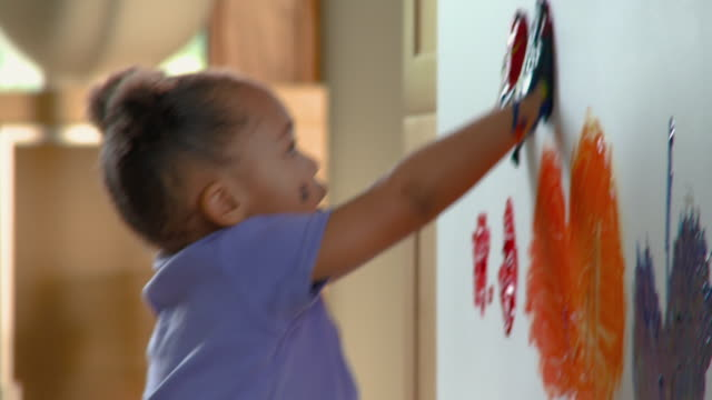 vidéos et rushes de cu rubbing paint on her hands and finger painting on wall / richmond, virginia, usa - art et artisanat