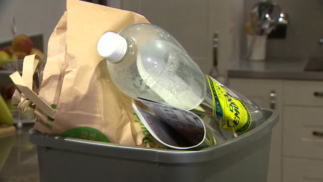 rubbish and plastic recycling and glass recycling put into different bins in kitchen - variation stock videos & royalty-free footage