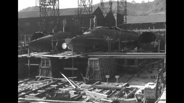 vs rubble and debris of demolished factory / submarines in various stages of construction amidst debris rubble / united states soldiers stand guard... - 1940~1949年点の映像素材/bロール