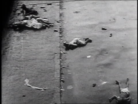 rubble in doorway / bodies lying in street / rescuers carrying injured person off street, using stretcher / bodies lying alongside road - anno 1947 video stock e b–roll
