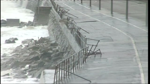 rubble on esplanade after the sea breached the sea wall high angle shot of broken railings along promenade / sea front and waves crashing over bv... - human limb stock videos & royalty-free footage