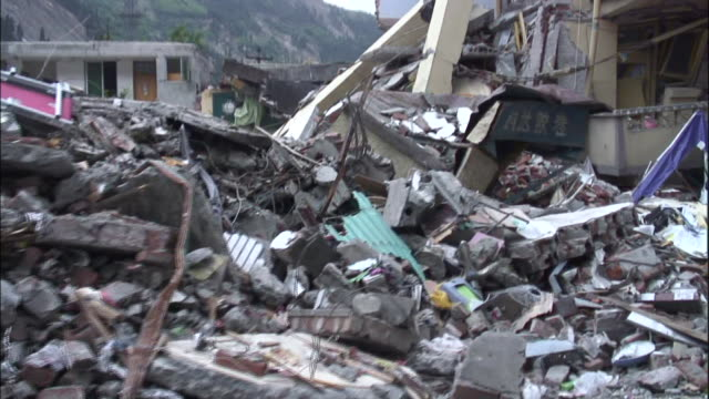 rubble piles high outside collapsed buildings in the aftermath of the sichuan earthquake - earthquake stock videos & royalty-free footage