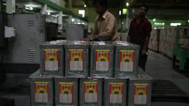 ruchi soya industries ltd employees move 15 liter tins of sunrich refined sunflower oil with a fork lift trolley at the company's edible oil refinery... - wrapping stock videos and b-roll footage