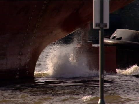 Rudder of large tanker cutting through water as it leaves port accompanied by tug boat Hamburg