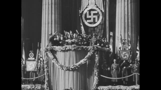 rudolf hess standing on platform with group of nazi officials administering oath they raise hands in nazi salute large swastika on stand behind them... - nazi swastika stock videos and b-roll footage