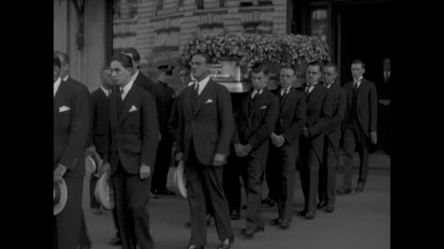 rudolph valentino's body on display at requiem mass with religious banner ihs representing the name of jesus christ in foreground / procession of men... - carro funebre video stock e b–roll