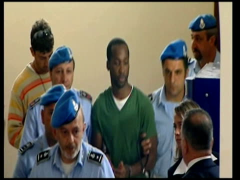 rudy hermann guede led into court by police meredith kercher murder trial on december 05 2009 in perugia italy - ペルージャ市点の映像素材/bロール
