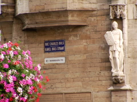 ms, rue charles buls street sign and statue on guild house, flowers in foreground, brussels, belgium - 道路名の標識点の映像素材/bロール