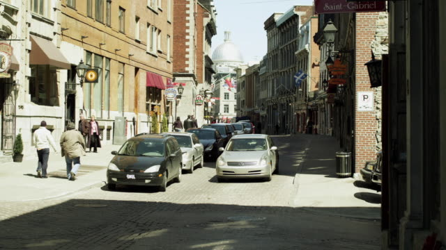 ws rue st paul in old montreal with bonsecour market in background / montreal, quebec, canada - ケベックの旗点の映像素材/bロール
