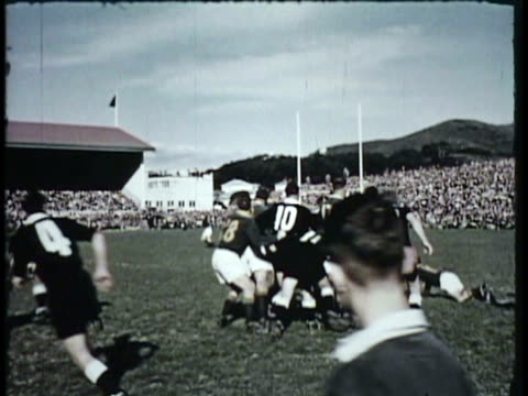 1955 montage ws pan ms rugby match, spectators cheering from tribunes, little league boys playing rugby / new zealand / audio - youth baseball and softball league stock videos and b-roll footage